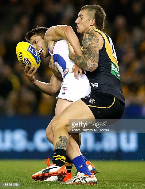Jamie Macmillan of the Kangaroos is tackled by Dustin Martin of the Tigers during the 2015 AFL round 23 match between the Richmond Tigers and the...
