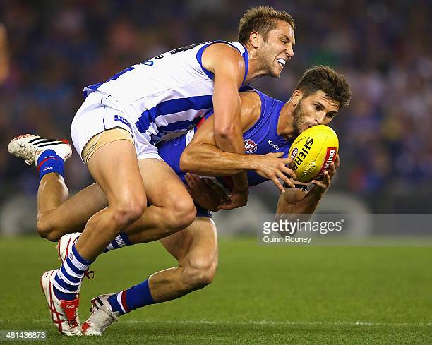 Jamie MacMillan of the Kangaroos tackles Koby Stevens of the Bulldogs during the round two AFL match between the Western Bulldogs and the North...