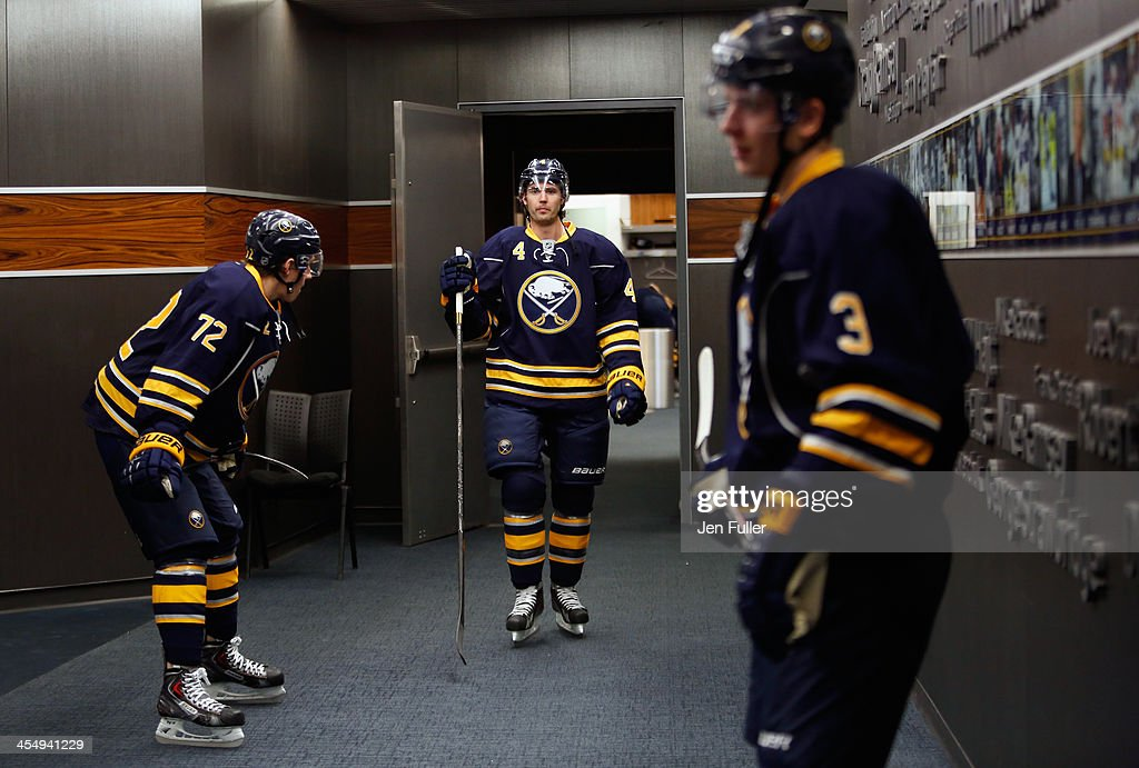 Jamie McBain Luke Adam and Mark Pysyk of the Buffalo Sabres prepare to take to the ice to warm up to play the Ottawa Senators at First Niagara Center...