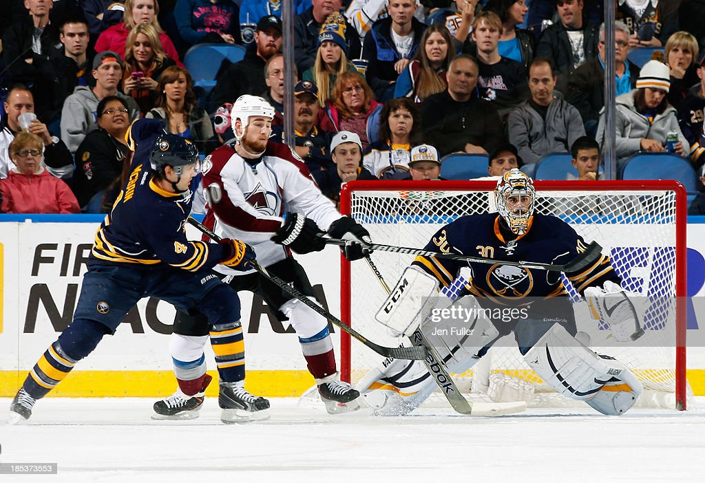 Jamie McBain #4 of the Buffalo Sabres and Ryan O'Reilly #90 of the Colorado Avalanche battle in front of the net as Ryan Miller #30 of Buffalo makes the save at First Niagara Center on October 19, 2013 in Buffalo, New York.