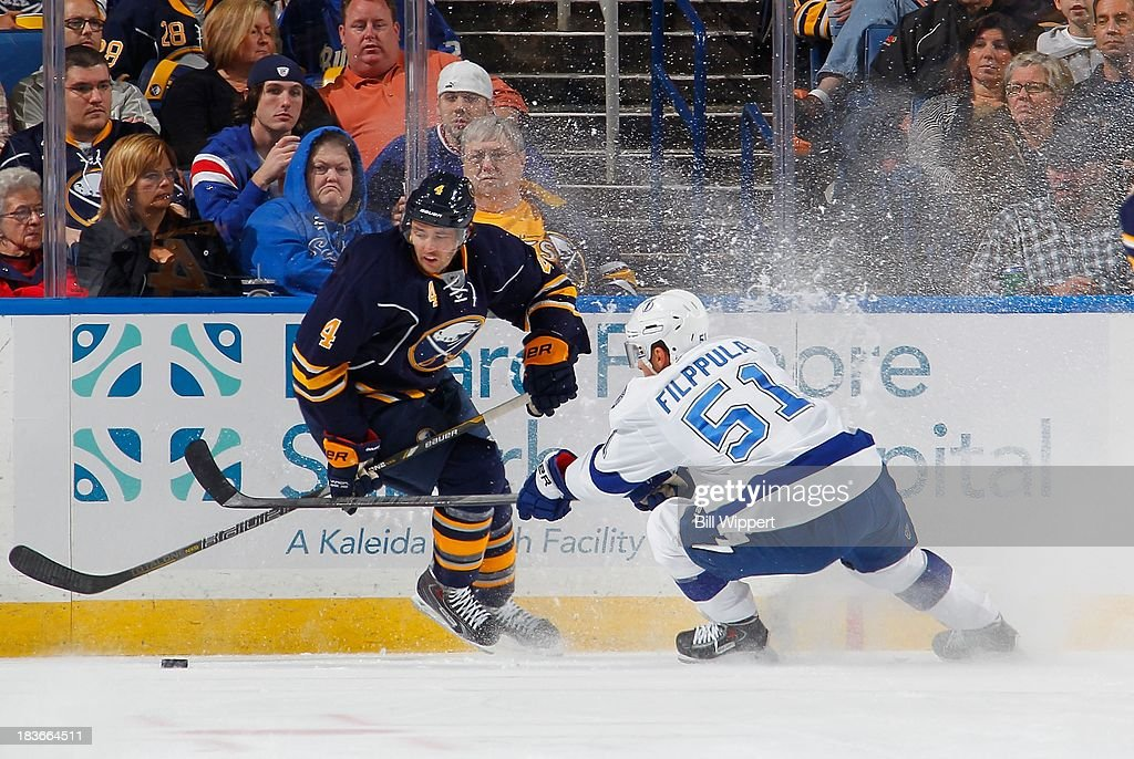 Jamie McBain #4 of the Buffalo Sabres battles for the puck with Valtteri Filppula #51 of the Tampa Bay Lightning on October 8, 2013 at the First Niagara Center in Buffalo, New York.