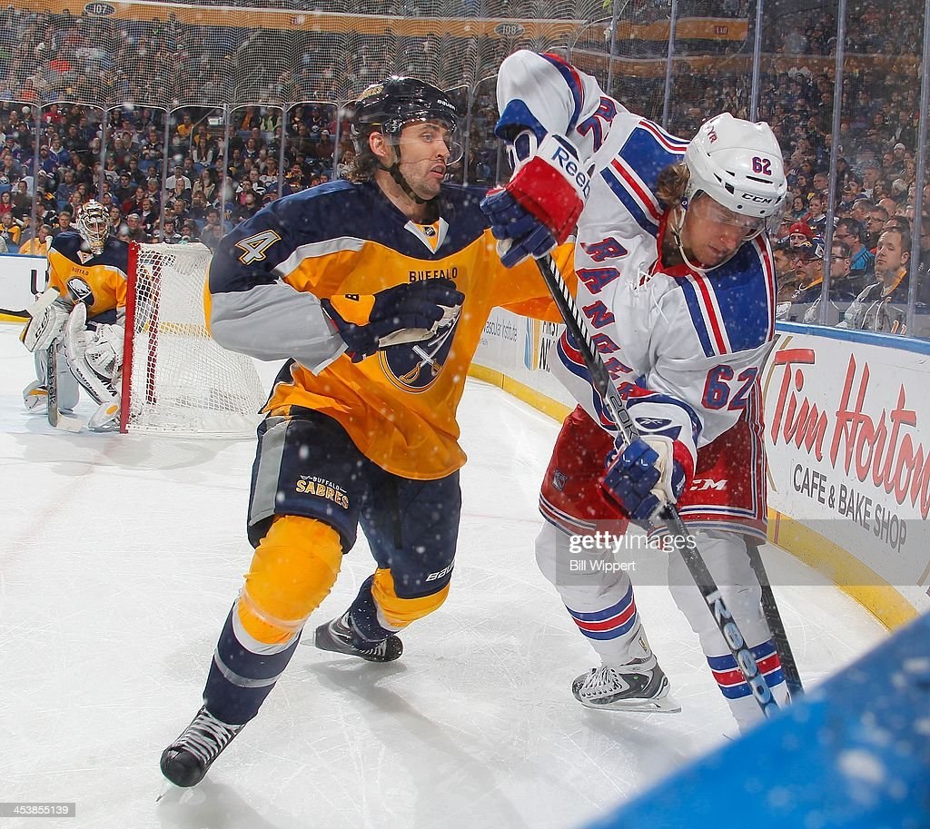 <a gi-track='captionPersonalityLinkClicked' href=/galleries/search?phrase=Jamie+McBain&family=editorial&specificpeople=543199 ng-click='$event.stopPropagation()'>Jamie McBain</a> #4 of the Buffalo Sabres defends <a gi-track='captionPersonalityLinkClicked' href=/galleries/search?phrase=Carl+Hagelin&family=editorial&specificpeople=4465394 ng-click='$event.stopPropagation()'>Carl Hagelin</a> #62 of the New York Rangers along the boards during the second period on December 5, 2013 at the First Niagara Center in Buffalo, New York.
