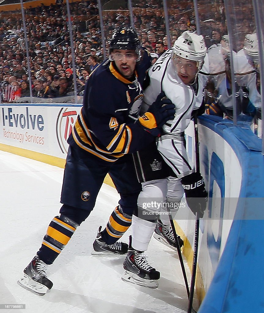 Jamie McBain #4 of the Buffalo Sabres holds Trevor Lewis #22 of the Los Angeles Kings against the boards during the first period at the First Niagara Center on November 12, 2013 in Buffalo, New York.