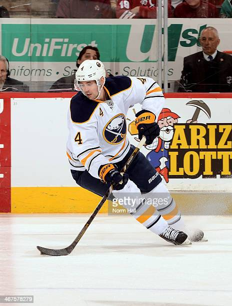 Jamie McBain of the Buffalo Sabres skates with the puck against the Phoenix Coyotes at Jobingcom Arena on January 30 2014 in Glendale Arizona