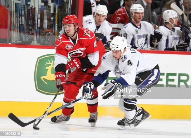 Jamie McBain of the Carolina Hurricanes battles for the puck against Vincent Lecavalier of the Tampa Bay Lightning during a NHL game on January 15...