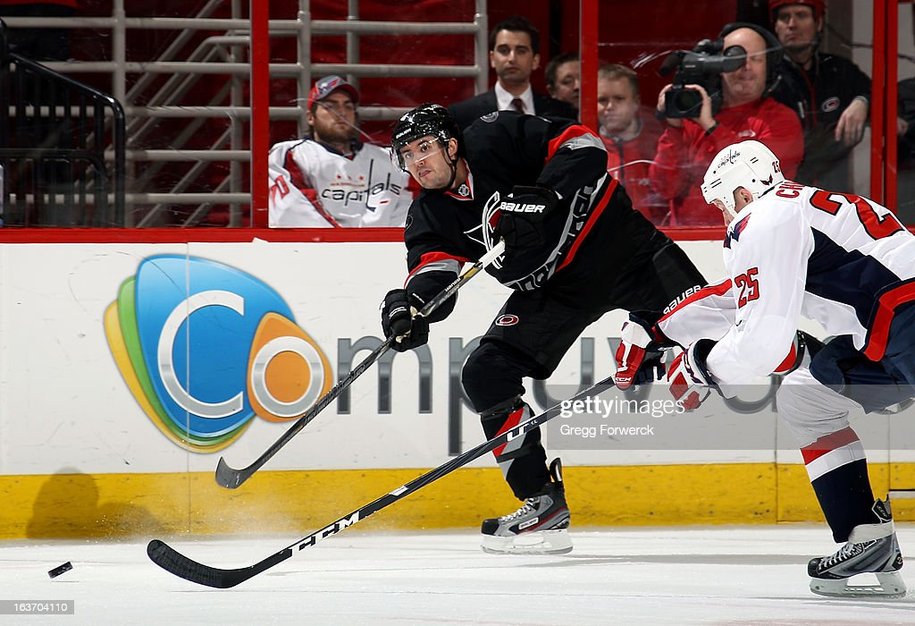 Jamie McBain #4 of the Carolina Hurricanes shoots the puck past the stick of <a gi-track='captionPersonalityLinkClicked' href=/galleries/search?phrase=Jason+Chimera&family=editorial&specificpeople=211264 ng-click='$event.stopPropagation()'>Jason Chimera</a> #25 of the Washington Capitals during their NHL game at PNC Arena on March 14, 2013 in Raleigh, North Carolina.