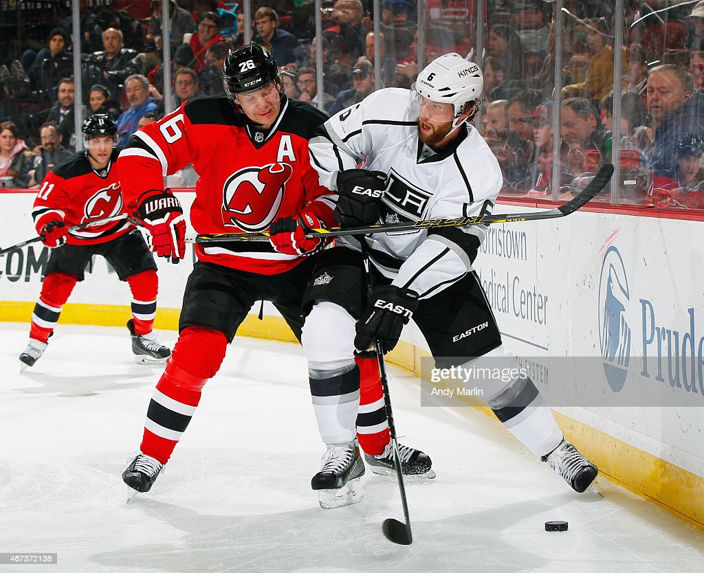 Jamie McBain of the Los Angeles Kings and Patrik Elias of the New Jersey Devils battle for the puck during the game at the Prudential Center on March...
