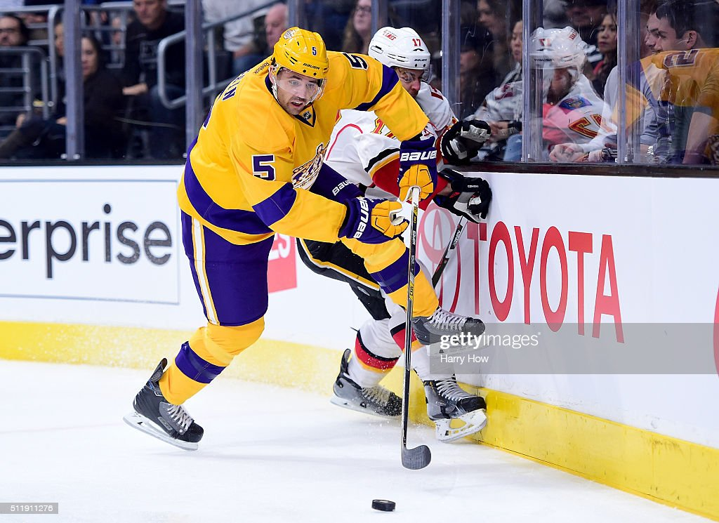 Jamie McBain of the Los Angeles Kings avoids a check from Lance Bouma of the Calgary Flames during the first period at Staples Center on February 23...