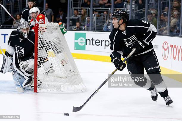 Jamie McBain of the Los Angeles Kings skates with the puck as Jonathan Quick of the Los Angeles Kings looks on during a game against the Florida...