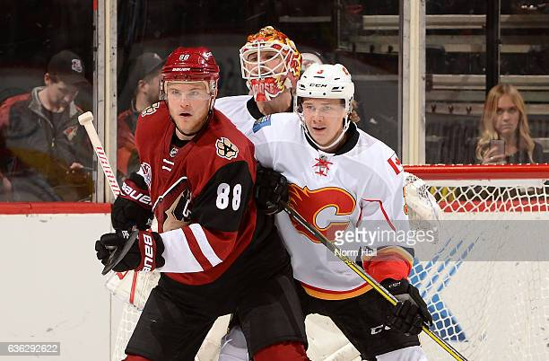 Jamie McGinn of the Arizona Coyotes and Jyrki Jokipakka of the Calgary Flames battle for position in front of Flames goaltender Brian Elliott at Gila...