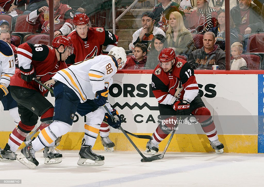 Jamie McGinn #88 of the Buffalo Sabres battles for the puck with Brad Richardson #12 and Jordan Martinook #48 of the Arizona Coyotes during the third period at Gila River Arena on January 18, 2016 in Glendale, Arizona. The Sabres defeated the Coyotes 2-1.