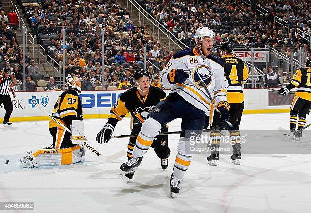 Jamie McGinn of the Buffalo Sabres celebrates his goal in front of Jeff Zatkoff and Olli Maatta of the Pittsburgh Penguins at Consol Energy Center on...