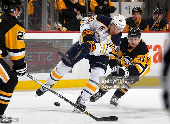 Jamie McGinn of the Buffalo Sabres moves the puck between the defense of Ian Cole and Kevin Porter of the Pittsburgh Penguins at Consol Energy Center...