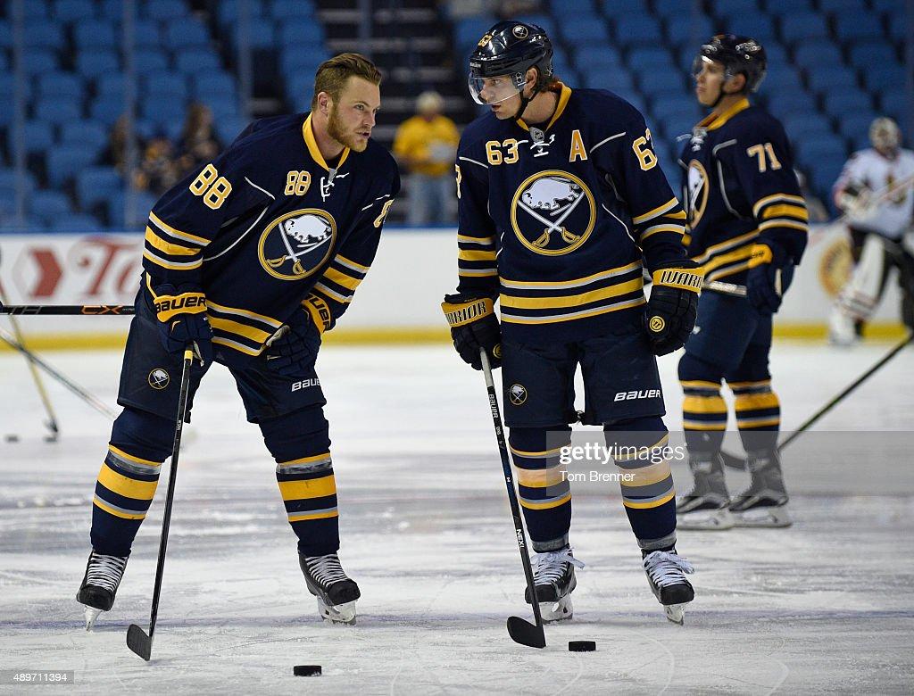 Jamie McGinn of the Buffalo Sabres talks to teammate Tyler Ennis of the Buffalo Sabres during warmups before a gaame against the Ottawa Senators at...