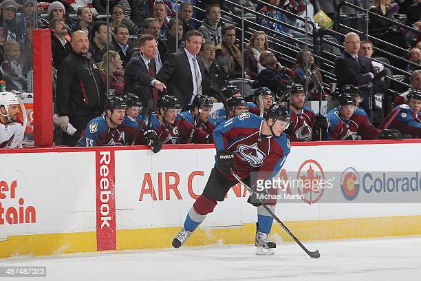 Jamie McGinn of the Colorado Avalanche handles the puck as head coach Patrick Roy and teammats look on against the Phoenix Coyotes at the Pepsi...