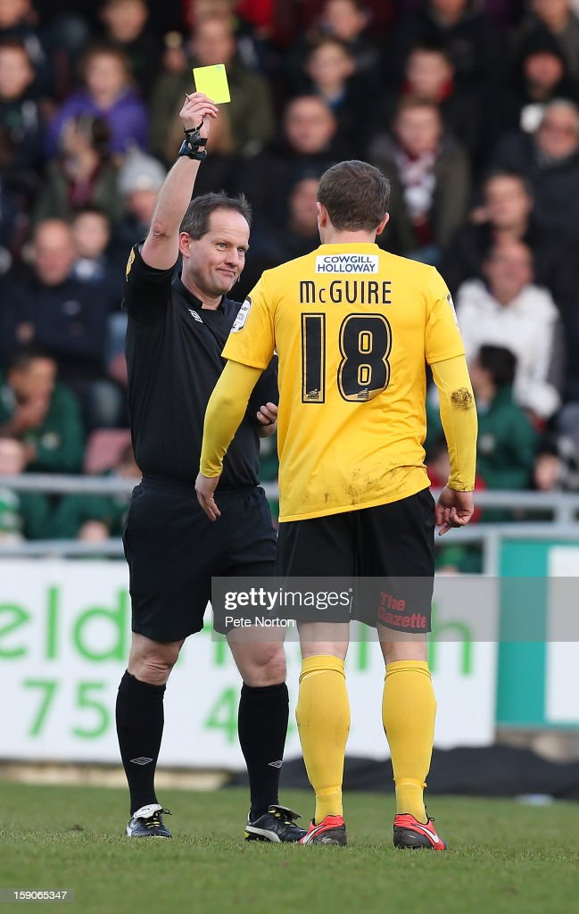 Jamie McGuire of Fleetwood Town is shown a yellow card by referee Rob Lewis during the npower League Two match between Northampton Town and Fleetwood Town at Sixfields Stadium on January 5, 2013 in Northampton, England.