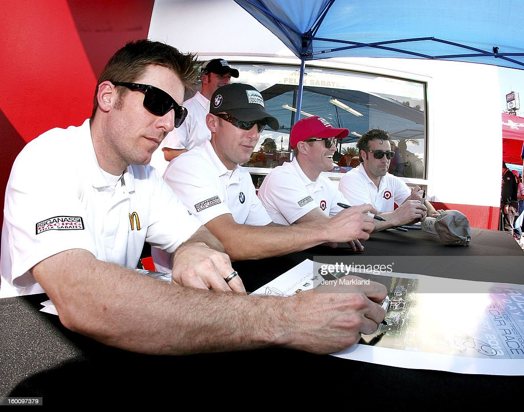 Jamie McMurray, co-driver of the #02 Chip Ganassi with Felix Sabates Target/TELMEX BMW Riley signs autographs along with co-drivers Joey Hand, Scott Dixon and Dario Franchitti at the Rolex 24 at Daytona International Speedway on January 26, 2013 in Daytona Beach, Florida.