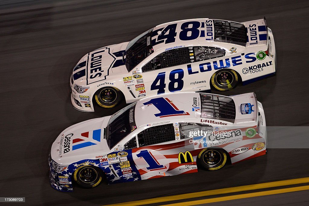 Jamie McMurray, driver of the #1 Cessna Chevrolet, and Jimmie Johnson, driver of the #48 Lowe's Dover White Chevrolet, race during the NASCAR Sprint Cup Series Coke Zero 400 at Daytona International Speedway on July 6, 2013 in Daytona Beach, Florida.