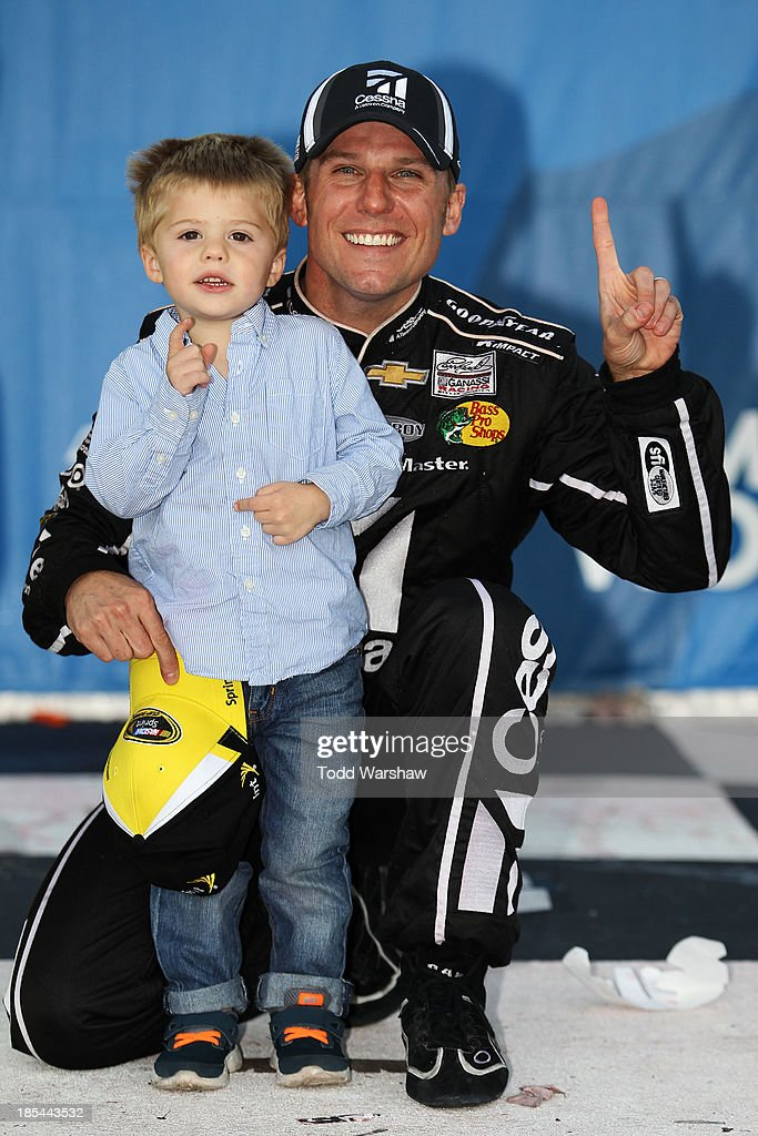 Jamie McMurray, driver of the #1 Cessna Chevrolet, celebrates in Victory Lane with his son Carter after winning the NASCAR Sprint Cup Series Camping World RV Sales 500 at Talladega Superspeedway on October 20, 2013 in Talladega, Alabama.