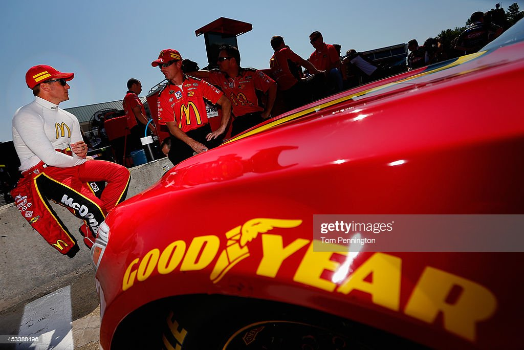 Jamie McMurray, driver of the #1 McDonald's Chevrolet, left, talks with his crew on the grid during qualifying for the NASCAR Sprint Cup Series Cheez-It 355 at Watkins Glen International on August 9, 2014 in Watkins Glen, New York.