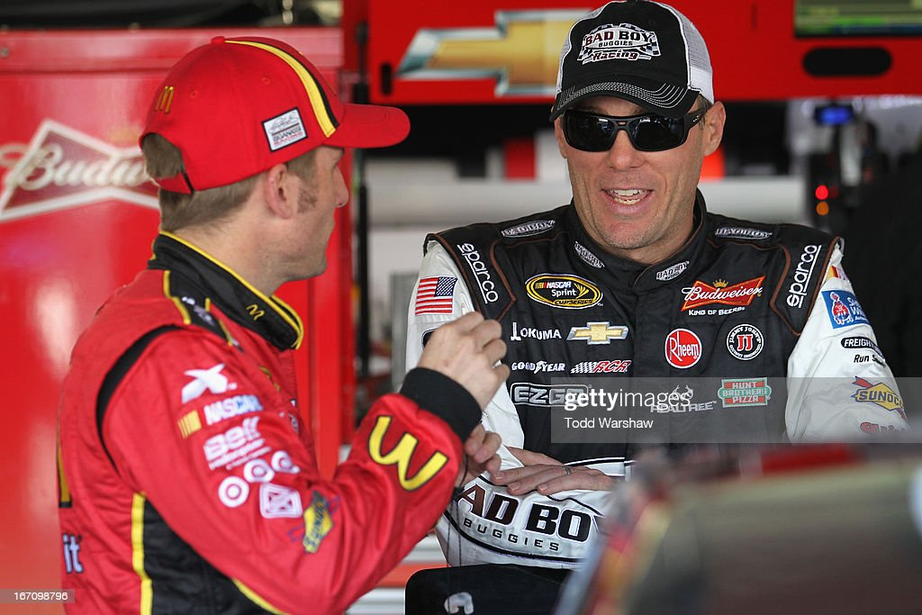 Jamie McMurray, driver of the #1 McDonald's Chevrolet, talks to Kevin Harvick, driver of the #29 Bad Boy Buggies Chevrolet, in the garage area during practice for the NASCAR Sprint Cup Series STP 400 at Kansas Speedway on April 20, 2013 in Kansas City, Kansas.