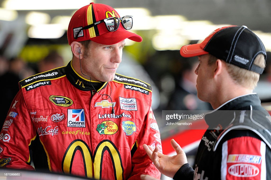 Jamie McMurray, driver of the #1 McDonald's Chevrolet, talks to Regan Smith, driver of the #51 Tag Heuer/Hendrickcars.com Chevrolet, during practice for the NASCAR Sprint Cup Series STP 400 at Kansas Speedway on April 20, 2013 in Kansas City, Kansas.