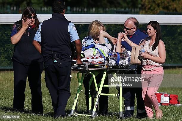 Jamie Mott is supported by his partner while taken on a stretcher to an ambulance after he fell while riding Zuma Roc in race 8 the LUCRF Super Hcp...