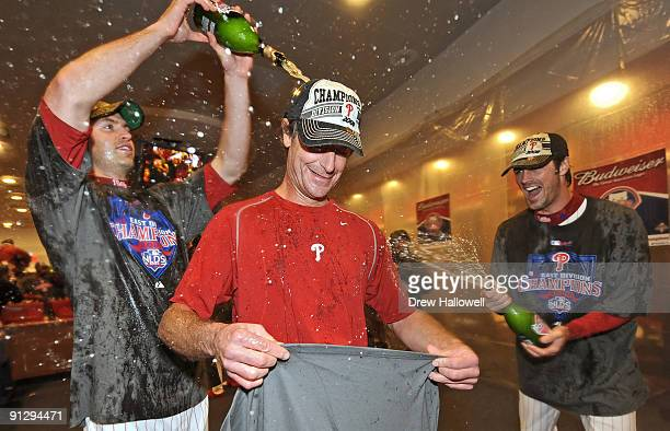 Jamie Moyer of the Philadelphia Phillies gets champagne pured on him by teammates JA Happ and Cole Hamels after beating the Houston Astros 103 and...
