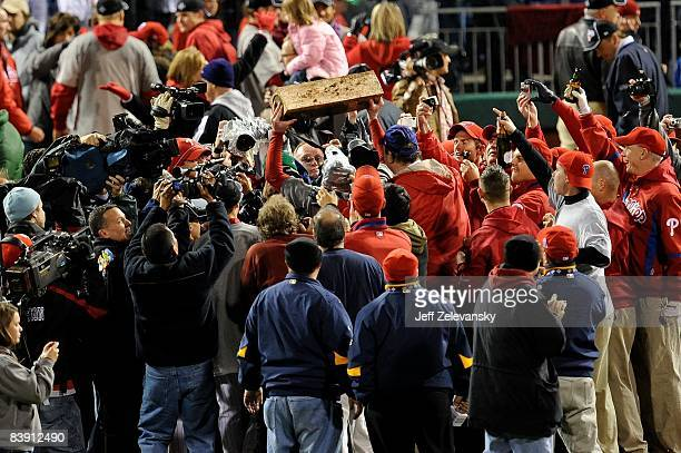 Jamie Moyer of the Philadelphia Phillies walks off the field carrying the pitcher's mound as he celebrate winning the World Series after their 43 win...