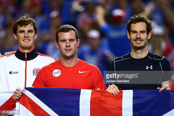 Jamie Murray Leon Smith and Andy Murray of Great Britain pose with Union Jack flags following victory on day three of the Davis Cup World Group first...