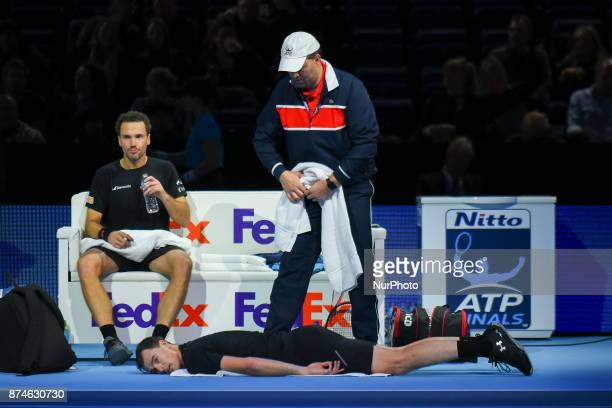 Jamie Murray of Great Britain partner of Bruno Soares of Brazil recieves treatment following an injury during the doubles match against Ivan Dodig of...