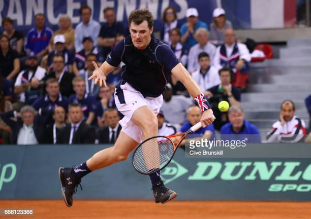 Jamie Murray of Great Britain partnering Dominic Inglot volleys in the doubles match against Julien Benneteau and Nicolas Mahut of France during the...