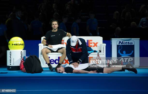 Jamie Murray of Great Britain receives medical assistance during a break as partner Bruno Soares of Brazil looks on during their victory over Ivan...