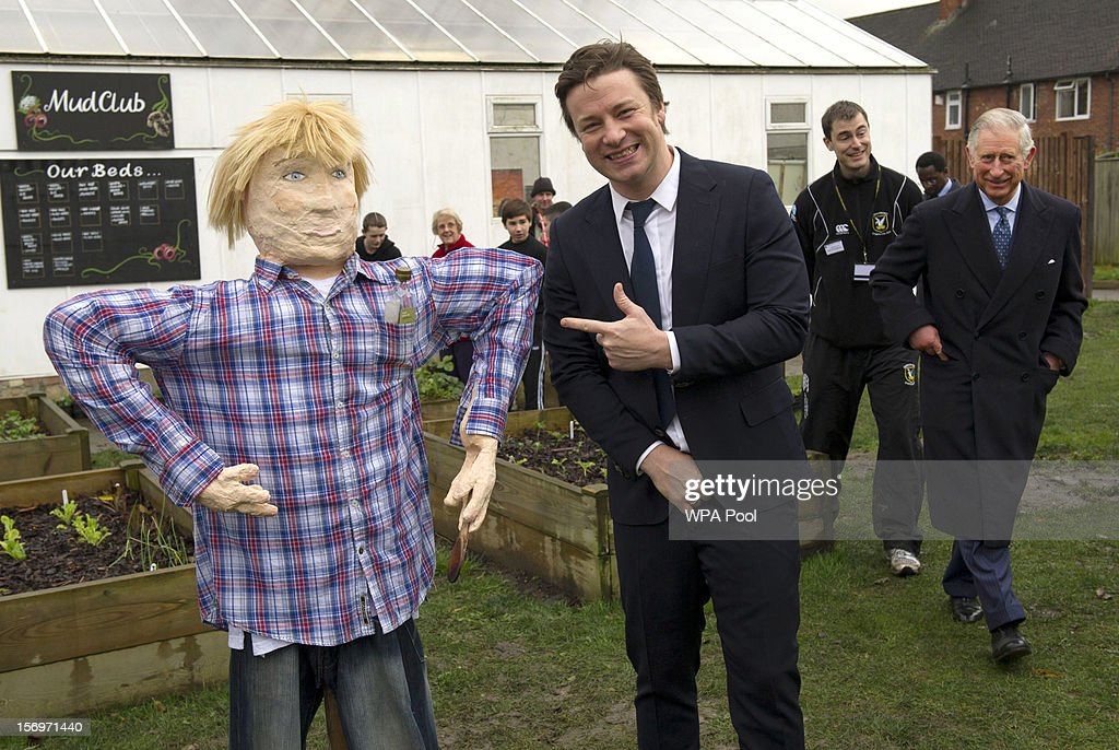 Jamie Oliver poses with a scarecrow next to Prince Charles, Prince of Wales during a visit to Carshalton Boys Sports College with Jamie Oliver to see how the school has transformed its approach to healthy eating on November 26, 2012 in Carshalton, England.