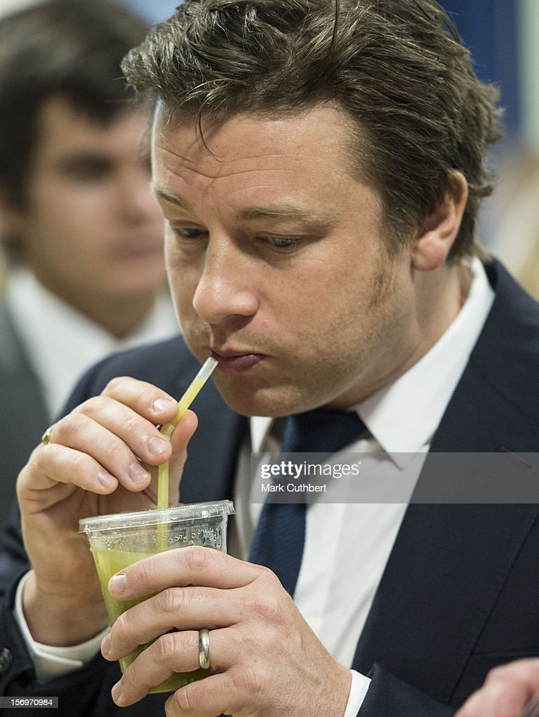 Jamie Oliver tries a fruit smoothie during a visit with Prince Charles, Prince of Wales to Carshalton Boys Sports college to see how the school has transformed its approach to healthy eating on November 26, 2012 in Carshalton, England.