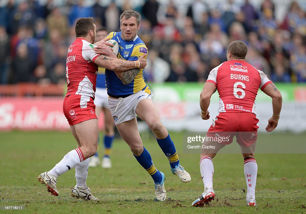 Jamie Peacock is tackled by Josh Hodgson and Travis Burns of Hull KR during the Super League match between Hull Kingston Rovers and Leeds Rhinos at Craven Park Stadium on April 28, 2013 in Hull, England.