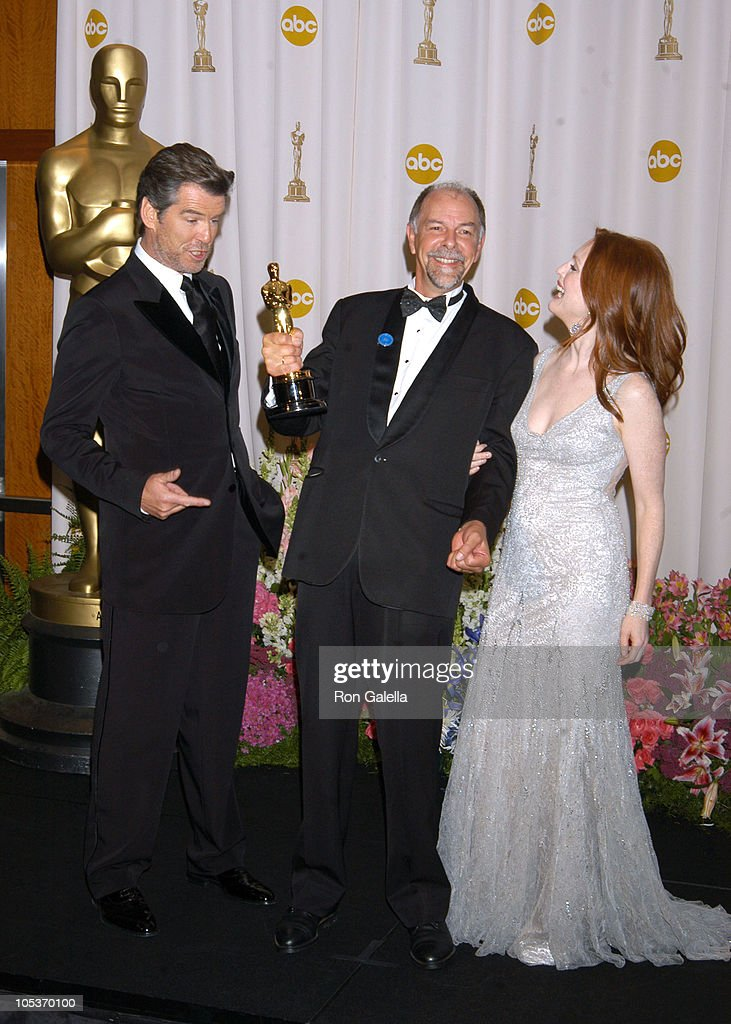 Jamie Selkirk (C), winner of Best Film Editing for 'The Lord of the Rings: The Return of the King', with presenters Pierce Brosnan and Julianne Moore