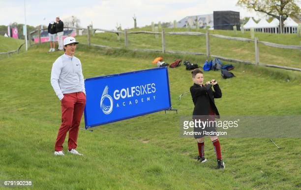 Jamie Simmons is watched by Thorbjorn Olesen of Denmark during a Golf Foundation GolfSixes Academy event at prior to the start of GolfSixes at The...