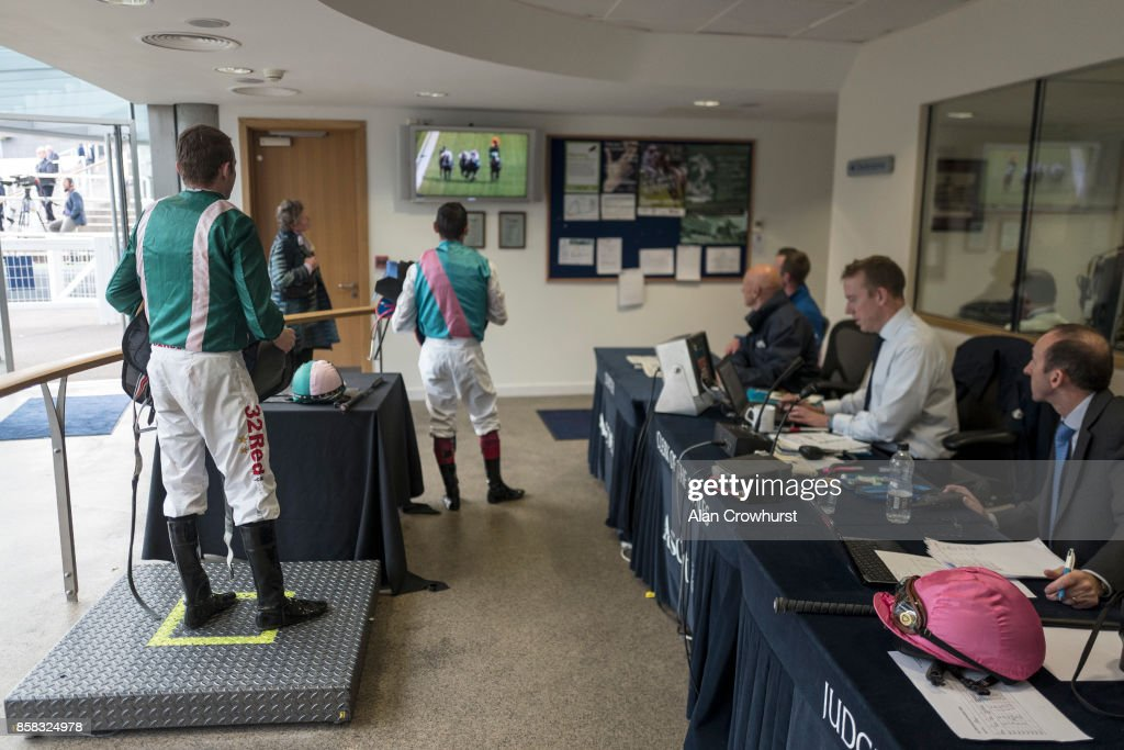Jamie Spencer (L) and Frankie Dettori (C) watch a replay in the weighing room before being called into a stewards enquiry at Ascot racecourse on October 6, 2017 in Ascot, United Kingdom.
