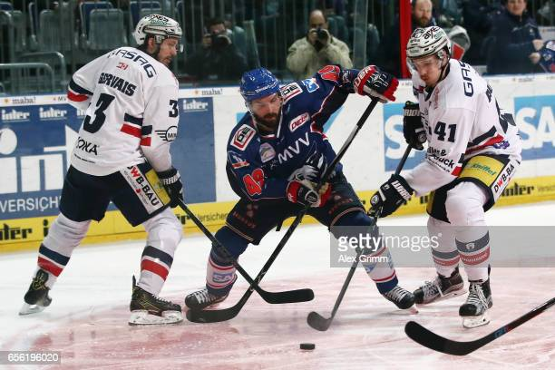 Jamie Tardif 8c9 of Mannheim is challenged by Bruno Gervais and LouisMarc Aubry of Berlin during the DEL Playoffs quarter finals Game 7 between Adler...