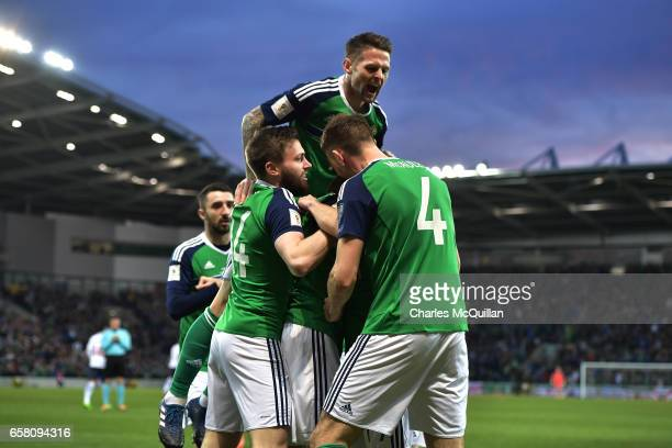 Jamie Ward of Northern Ireland is mobbed by team mates as he celebrates opening the scoring during the FIFA 2018 World Cup Qualifier between Northern...