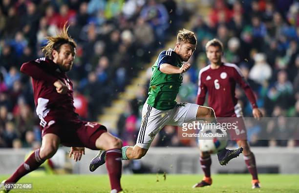 Jamie Ward of Northern Ireland shoots wide watched by IgorsTarasovs of Latvia during the international football friendly at Windsor Park on November...