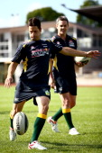 Jamie Whincup and Craig Lowndes of Red Bull Racing kick a rugby ball during a joint light training run with some of the New Zealand Warriors at Mt...