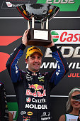 Jamie Whincup driver of the Red Bull Racing Australia Holden Commodore VF celebrates on the podium after winning race 1 for the Townsville 400 at...