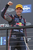 Jamie Whincup driver of the Red Bull Racing Australia Holden celebrates winning the champtionship after finishing third in the Sydney 500 which is...