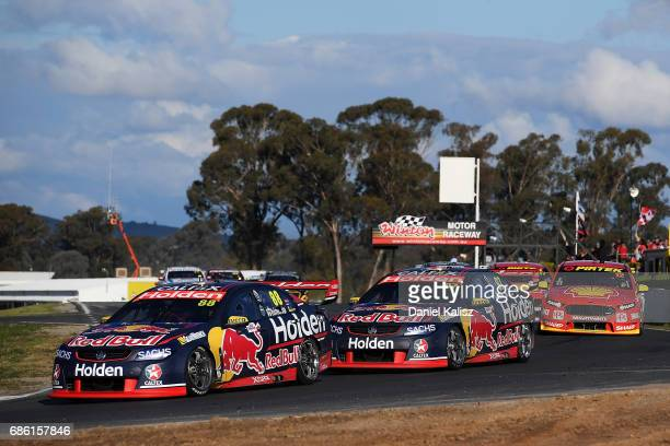 Jamie Whincup drives the Red Bull Holden Racing Team Holden Commodore VF leads Shane Van Gisbergen drives the Red Bull Holden Racing Team Holden...