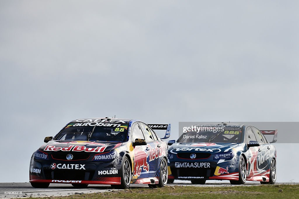 Jamie Whincup drives the Red Bull Racing Australia Holden Commodore VF leads Craig Lowndes drives the TeamVortex Holden Commodore VF during race 2...