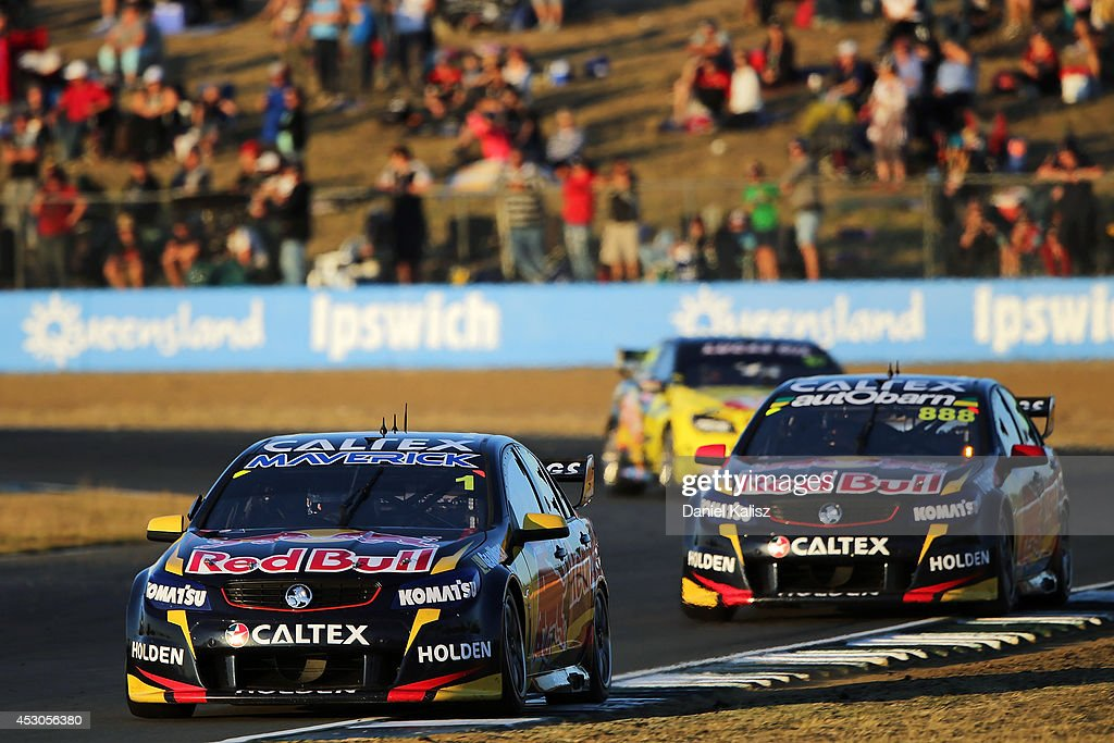 Jamie Whincup drives the Red Bull Racing Australia Holden leads Craig Lowndes drives the Red Bull Racing Australia Holden during race 24 for the...