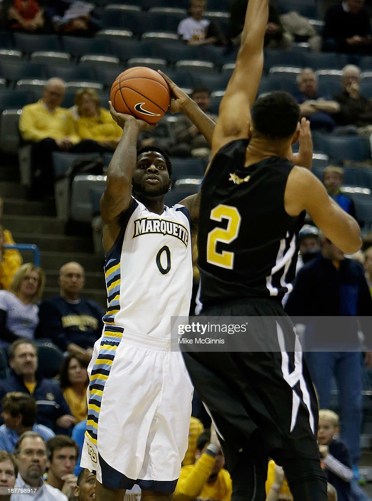 Jamil Wilson #0 of the Marquette Golden Eagles pulls up for a three pointer in the corner with Richard Freeman #2 of the Grambling State Tigers defending during the first half of play at BMO Harris Bradley Center on November 12, 2013 in Madison, Wisconsin.