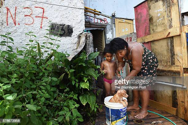 Jamilly Vitoria Santos da Silva center stands next to her mother Rebeca Arruda right as they wash a dog in a bucket in a favela as members of the...